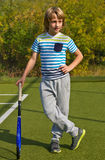 Boy standing with tennis racket and ball on the court Royalty Free Stock Photos
