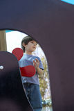 Boy (4-6) standing beside toy windmill in playground, focus on background Royalty Free Stock Images