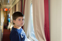 Boy standing at train window Stock Photos