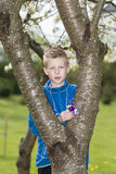 Boy standing by a tree with a collection of wild flowers Royalty Free Stock Photography