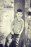 Boy Standing by Tree Stock Photos