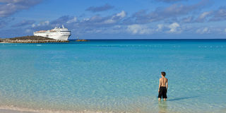 Boy standing on tropical beach with cruise ship royalty free stock photos