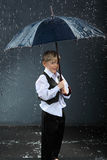 Boy standing under umbrella in rain Stock Photo