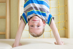Boy standing upside down in gym class. Stock Image