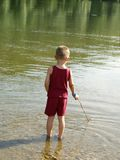 Boy standing in the water Stock Photography
