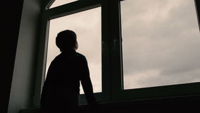 Boy standing at window and look at the sky