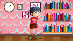A boy standing beside the wooden shelves with books Royalty Free Stock Image