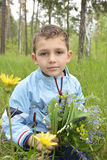 Boy standing in the woods with a bouquet of flowers. Royalty Free Stock Photos