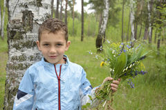 Boy standing in the woods with a bouquet of flowers. Stock Photography