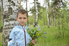 Boy standing in the woods with a bouquet of flowers. Stock Images