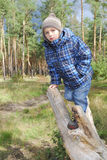 Boy standing in the woods on a log. Royalty Free Stock Photos