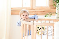 A boy stands alone beside a cot in the nursery. Lonely baby is in kindergarten near the crib. Loneliness. Eco-friendly children`s. Room decor in the stock photography