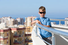 A boy stands on balcony of hotel Royalty Free Stock Photo