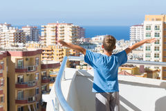 A boy stands on the balcony of the hotel Royalty Free Stock Images