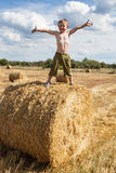 Boy stands on bale straw Royalty Free Stock Photography