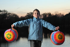 Boy stands on bank of river with paper balls Stock Images