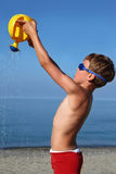 Boy stands on beach and pours sand watering-can Royalty Free Stock Image