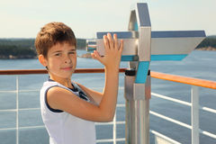 Boy stands on board of ship near binoculars Stock Image