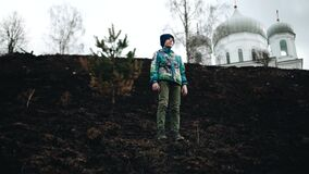 The boy stands on the burnt grass on a steep slope and looks ahead. Cool landscape