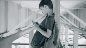 The boy stands in a cool metal corridor. Atmospheric shots. The boy looks at the smartphone. It`s under the bridge. Black and white frames stock footage