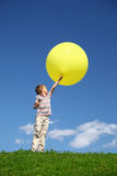 Boy stands in field and lifts balloon Royalty Free Stock Photography