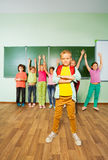 Boy stands in front of children with hands up Stock Photo