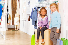 Boy stands and girl sits with shopping bags Stock Photo