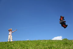 Boy stands on grass and starts kite Stock Photography
