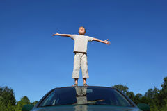 Boy stands on head of auto lifting head to sky Stock Images