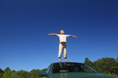 Boy stands on  head of auto, sends hands in sides Royalty Free Stock Image