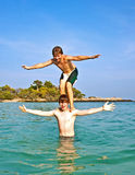 Boy stands on his brother's shoulders in an ocean bay Royalty Free Stock Image