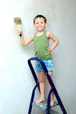 A boy stands on a ladder with a brush in his hand Stock Photography