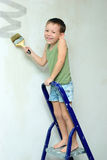 A boy stands on a ladder and paints the wall Royalty Free Stock Photo