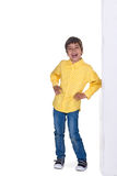 The boy stands and laughs. The boy in a shirt and jeans stands and laughs stock image
