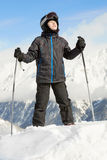 Boy stands leaning on ski poles and looking upward Stock Images