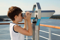 Boy stands and looks through binoculars Royalty Free Stock Photos