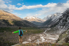 Boy stands on a mountain in a green jacket with a blue backpack on the background of the gorge and snow-capped mountains royalty free stock photography