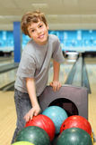 Boy stands near balls in bowling club Royalty Free Stock Image