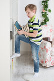 Boy stands near a bookcase with books Royalty Free Stock Images
