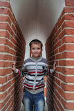 Boy stands near the brick wall Stock Images