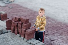 The boy stands near the building bricks. laying paving slabs . Children and the profession. The boy stands near the building bricks. laying paving slabs . gray royalty free stock images