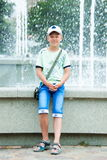 Boy stands near a fountain Royalty Free Stock Images