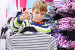 Boy stands near shelves with shirts Stock Photo
