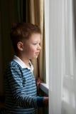 Boy stands near the window Stock Photos