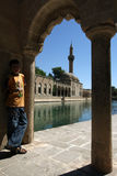 A boy stands next to Balikli Gol (Pool of Sacred Fish) in Urfa (Sanliurfa). Royalty Free Stock Photo