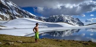 A boy stands next to the mountain lake in front of snow mountains in the sunny and cloudy day stock photography
