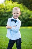Boy stands in a park on a green background Royalty Free Stock Photos
