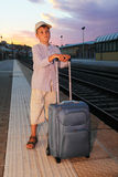 Boy stands on platform of railway with travel bag Royalty Free Stock Photography