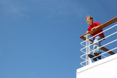 Boy stands at railing on deck of ship Stock Images