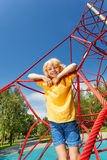 Boy stands on red ropes of net in the park Stock Images